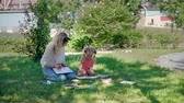 ressam : Little Girl with Teacher at Drawing Lesson Outdoors. Watercolor Paint with Teacher in Nature. Slow Motion. Development of Childrens Artistic Creativity and Thinking Stok Video