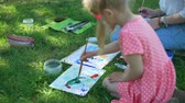 petites filles dessin : Child Holding a Painting Lesson and Art Class in Nature. Little Girl Mixing Colors by Brush for Drawing Outdoors. Learning to Draw. Slow Motion. Art School, Creativity and People concept