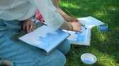 petites filles dessin : Watercolor Painting with Teacher in City Park in Summer Day in Slow Motion. Art School Classes Outdoors. Painting Courses. Student and Teacher Drawing Together. Vidéos Libres De Droits