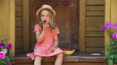 morango : Cute Young Girl in Straw Hat Eating Fresh Strawberry while Sitting on the Porch of a Country House. Summer Vacations and Lifestyle Concept