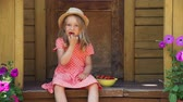 strawberry : Little Girl in Straw Hat Eating Fresh Strawberry while Sitting on the Porch of a Country House. Slow Motion. The Concept of a Happy Childhood