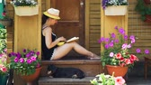 morango : Young Woman Reading a Novel and Eating Natural Strawberries while Sitting on the Porch of the Country House. The Dachshund Dog Lying near Her. Slow Motion. Summer Vacations and Lifestyle Concept