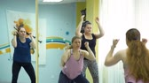 plusz : Woman Doing Physical Exercises with Personal Trainer near Big Mirror. Workout for Overweight Women in a Fitness Centre for Weight Losing. Stock mozgókép