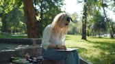 esboçar : Female Artist Preparing a Sketch for Future Picture in Slow Motion. Professional Painter at Work in a City Park in Sunny Summer Day. Creativity Inspiration Expression Concept Stock Footage