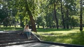 obra prima : Female Artist Drawing with Pencil Outdoors in Slow Motion. Street Artist Painting in the City Park in Summer Day. Wide Shot. Creativity Inspiration Expression Concept
