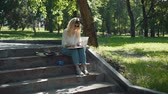 esboçar : Professional Painter Working in a City Park in Sunny Summer Day while Sitting on Steps. Female Street Artist Doing a Sketch for Future Picture Outdoors. Creativity Inspiration Expression Concept Stock Footage