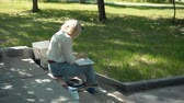 szkic : Female Street Artist Painting a Picture at the Paper while Sitting on Steps of City Embankment. Creativity Inspiration Expression Concept