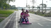 inline : Little Girl and her Mother Having Fun after Rollerblading in Slow Motion. They are Sitting on the Bicycle Lane in a City Park in Sunny Day. Summer Family Activities Concept Stock Footage