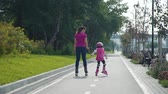 inline : Young Mother Roller Skating with her Daughter Outdoors. Young Woman Teaching Little Girl to Rollerblading in Sunny Day. Summer Family Activities Concept