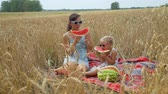 groen tarwe veld : Little Girl and her Mother Eating Watermelon in a Wheat Field in Autumn Day. Slow Motion. Family, Leisure and People Concept