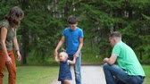 four children : Cute Baby Girl Walking with Parents and Brother Outdoors. Child Making First Steps. Happy Childhood and Child Development Concept Stock Footage