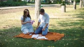 analık : Young Man and Woman Looking at Clothes for Their Future Baby in Autumn City Park. Pregnant Couple Preparing to Become Parents. Pregnancy, Maternity, Preparation and Expectation Concept