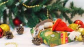 ratti : Little Rat Eating Piece of Cheese near Christmas Tree while Sitting on the Present Box. Slow Motion. The Symbol of the New Year 2020 in the Chinese Calendar. New Year and Christmas Concept