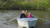 koponya : Young Family Boating Together on Autumn Day with Cute Puppy in a Boat. Leisure, Wild Nature and People Concept Stock mozgókép