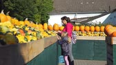 販売の : Young Woman and her Cute Little Daughter Shopping at Local Farmers Market. Large Piles Scattering of Orange Pumpkins and Gourds at a Pumpkin Patch. Halloween Harvesting and Thanksgiving Concept 動画素材