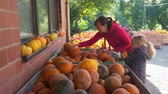 販売のための : Young Woman with her Cute Daughter Shopping at Local Farmers Market. An Assortment of Autumn Pumpkins. Natural Organic and Vegan Food Shopping Concept