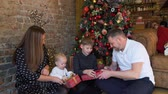 boite cadeau : Children Unpacking Christmas Presents. Happy Family in the Room with the Christmas Tree. Slow Motion. Winter Holiday Celebration and People Concept Vidéos Libres De Droits