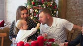 four children : Young Family at Dinner Table near Christmas Tree. Cute Little Girl Treating her Father. Slow Motion. Winter Holiday Celebration and People Concept Stock Footage