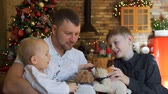 bratr : Father and his Two Children Enjoying Their Time Together. Man Playing with Kids while Sitting on a Sofa near Christmas Tree. Slow Motion. Winter Holiday Celebration and People Concept Dostupné videozáznamy