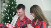 pyjama : Young Woman Giving a Christmas Present to her Boyfriend. Loving Couple Spending Christmas Time Together. Winter Holiday Celebration and People Concept