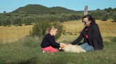 toszkána : Young Mother with her Daughter Petting the Dog in Sunny Day. Beautiful Olive Grove and Tuscan Hills are on the Background. Pets and Animals Concept