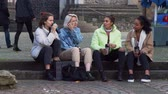 Group of Mixed Race Girlfriends Drinking Coffee or Tea and Talking while Sitting on the Steps in the Old European City. People, Leisure, Friendship and Communication concept