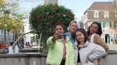 Mixed Race Teen Girlfriends Taking Selfie by Smartphone on a German Street over the Fountain. They Showing Tongue and Peace Gesture. Friendship, Lifestyle and People Concept Stock mozgókép
