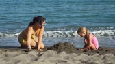 Young Mother Playing with her Daughter on the Sand Beach. They Building Sand Castle. Concept of Family Holidays and Vacation