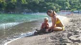 Young Mother and her Little Daughter Building Sand Castle on the Beach in Sunny Summer Day. Lots of Deck Chairs and Flag of Italy are on the Background. Concept of Holidays, Vacation and World Travel Stock mozgókép