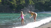 Young Mother and her Little Daughter Playing in a Water on the Beach. They Smiling and Splashing Water. Slow Motion. Concept of Summer Holidays, Vacation, Family and People Stock mozgókép