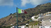 ulusal bayrağı : Italian Flag with National Emblem Fluttering in the Wind in Slow Motion. Beautiful Town of Sant Angelo on Ischia Island is on the Background. Concept of Holidays, Vacations and World Travel Concept Stok Video