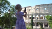 coliseu : Cute Little Girl in Violet Dress Taking Photos of Coliseum or Colosseum with Smartphone in Rome. Concept of Holidays, Vacations and Travel in Europe
