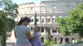 coliseu : Smiling Little Girl with Mother Sitting and Talking over Colosseum (Coliseum) in Rome. Family Holidays, Vacation and People Concept