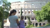coliseu : Young Mother with her Cute Little Daughter Sitting near Coliseum (Colosseum) with Smartphone in Rome. Back View. Family Holidays, Vacation and People Concept