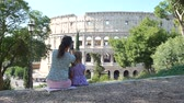 coliseu : Young Mother with her Cute Little Daughter Taking Photos of Colosseum (Coliseum) with Smartphone in Sunny Day. Concept of Holidays, Vacations and Travel in Europe