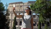 coliseu : Beautiful Young Woman Taking Selfie with Smartphone near Colosseum or Coliseum in Rome. She is Enjoying Vacation in Europe. Concept of Holidays, Vacations and World Travel Stock Footage