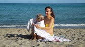 strandlaken : Young Happy Mother Covering her Little Daughter with a Towel on a Beach after Swimming. Slow Motion. Concept of Summer Holidays, Vacation, Family and People