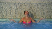 banheira : Young Woman Relaxing Under a Waterfall Jet at a Pool. Slow Motion. Spa Hydrotherapy and Relax Concept