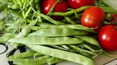 nourishment : In the kitchen there is green beans, tomatoes and fine pepper,