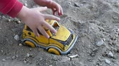 hoe : playing with a child in the soil, child playing in the soil with toy car.