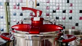 utensili da cucina : pressure cooker boiling, steam cooker, pressure cooker extracting steam on the cooker.