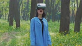 head mounted display : VR headset on woman outdoors. Portrait of brunette lady wearing VR glasses. Virtual reality helmet on caucasian woman in park or forest. VR headset on attractive girl in blue coat.