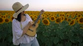 blossom : Happy woman in sunflower field playing on ukulele and singing. Summer girl in cowboy straw hat. Caucasian young lady have fun. Slow motion. Little guitar. music concept.
