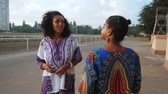 hipster : Two happy beautiful afro-american women friends talking outdoor. Multi ethnic girls wearing colorful clothing communicates, enjoys the meeting and laughing in slow motion. Dolly shot. Stock Footage