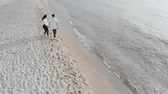 bahamské ostrovy : Aerial drone view above couple in love walking on sandy sea beach. Pair are in love, having good time, enjoying life. Romantic concept. Dostupné videozáznamy
