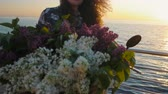 flor cabeça : Adult cute woman in dress with vintage retro bicycle and basket full of lilacs near sea during sunrise. Portrait of smiling caucasian young lady with sun flares. 4k