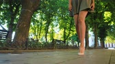 elite : Sexy legs with high beige heels walking in park of city. Woman walking on boulvard alone. Attractive girl in short dress at summer season. Slow motion.