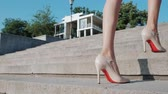 elite : Sexy legs with high beige heels climbs stairs of city. Business woman walking on boulvard alone. Attractive girl in short dress at summer season. Slow motion. Stock Footage