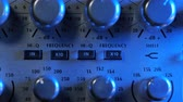 véu : Adjustable handles on the compressor panel in professional recording studio. Blue neon light. Sound mixing concept. Dolly shot. 4k. Stock Footage