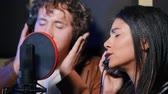 compositor : Young team of singers performing song in record studio.Professional musician duet recording new album.Beautiful couple working and singing near microphone together.Slow motion. Vídeos
